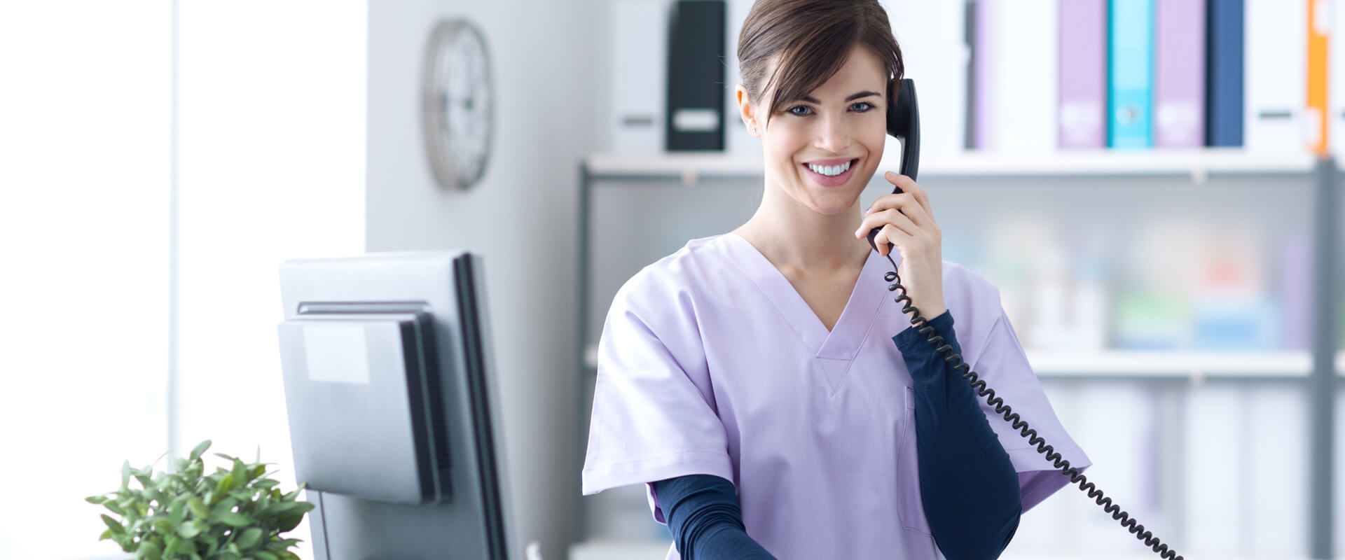 Receptionist at dental clinic answering phone call