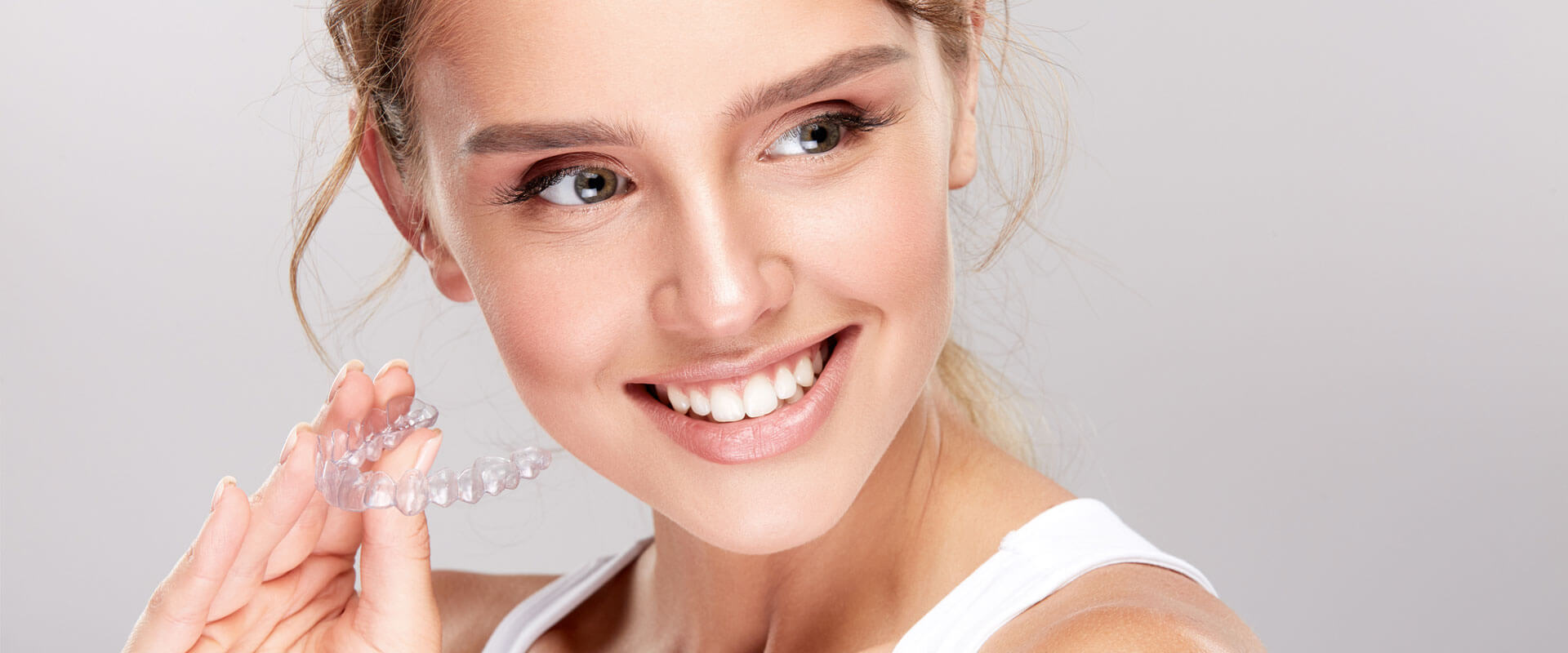 Smiling young woman holding Invisalign braces