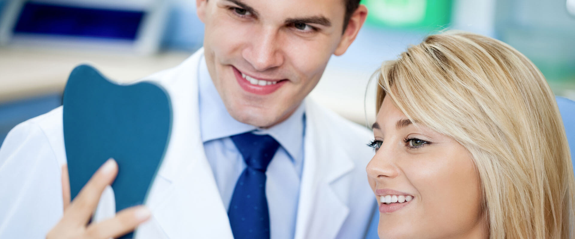 Dentist and satisfied patient smiling looking at white teeth