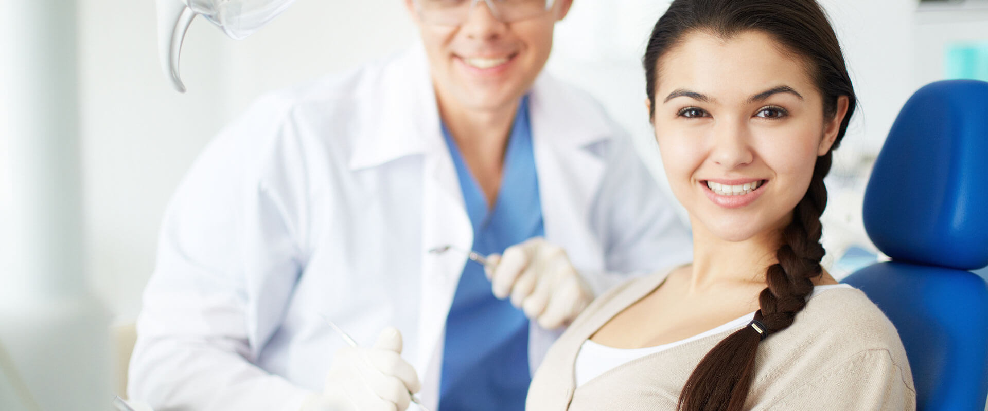 Smiling woman seated on dental chair awaiting root canal treatment