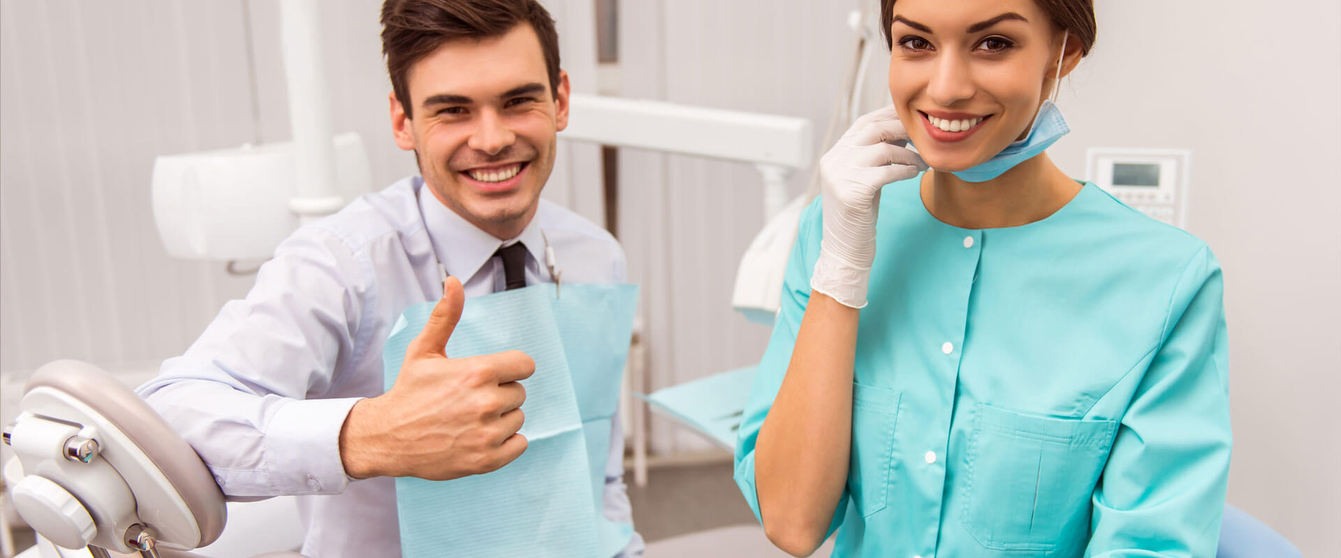 Patient showing thumbs up while assistant smiling at dental clinic