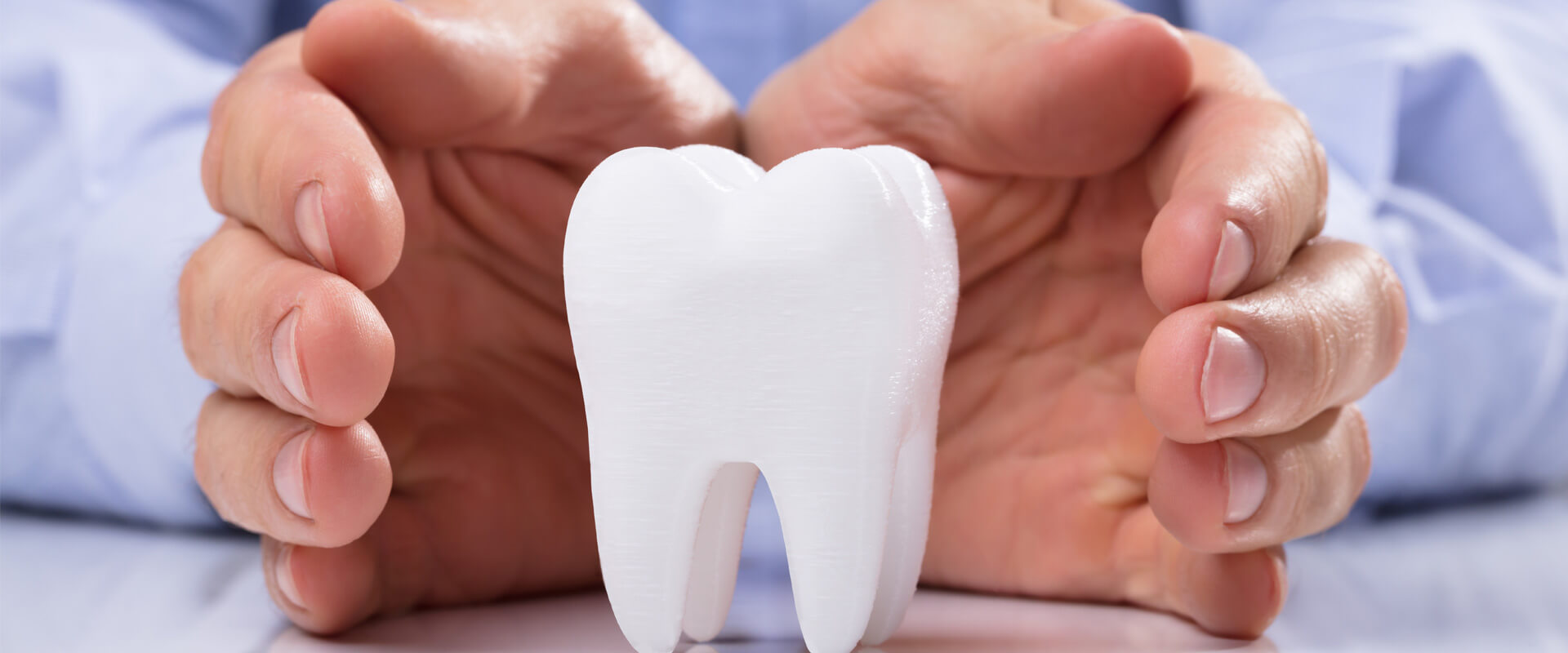 Closeup of a dental crown structure protected by two hands